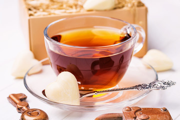 Foto op Canvas Thee Cup of black tea with chocolates in the shape of a heart, lock, key