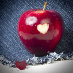 Fresh red apple with a heart shaped cut-out on jeans background. GMO free genetically modified organisms. Valentine day.
