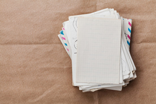 Stack of old envelopes and letters on kraft paper, top view