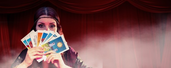 Fortune teller hiding mouth with cards