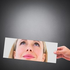 Composite image of hands showing photo of smiling woman