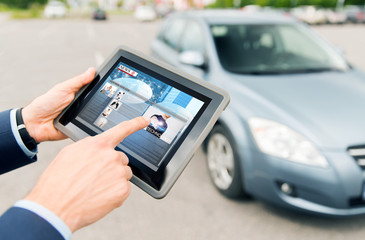 close up of hands with news on tablet pc and car