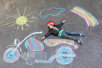 Little kid boy in helmet with motorcycle chalk picture
