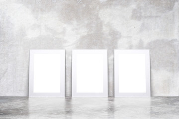 Blank white picture frames in empty loft room with concrete floo