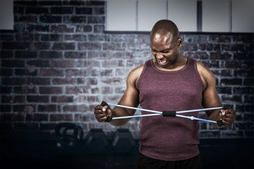Composite image of fit man exercising with resistance band