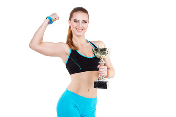 Young red-haired athlete woman poses with the championship trophy. She has strong big biceps. She is happy and smiles brightly.