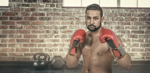 Composite image of muscular man boxing in gloves