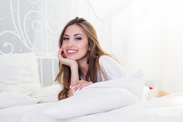 Pretty smiling girl is lying in bed with white pillows