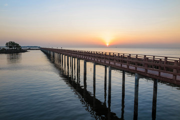 The wooden bridge in the sea with sunrise in the morning
