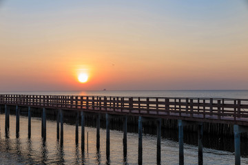 Sunrise in the morning with the wooden bridge view in the sea