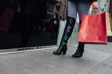 Black women's boots and red shopping bag