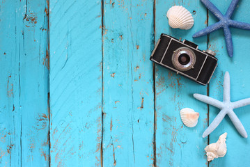 top view image of photo camera, sea shells and star fish over wooden table