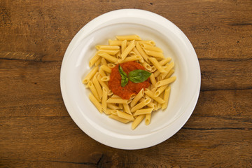 Top view of penne arrabiata with basil leaves in white porcelain plate on wooden table