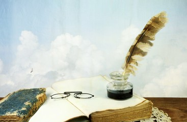 Desk with old books, pince-nez and inkwell on background of sky