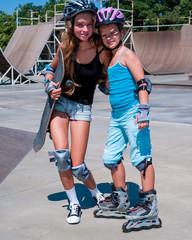 Children in helmet skateboarding on his skateboard and rollerskates