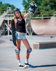 Teen girl sitting on his skateboard outdoor.