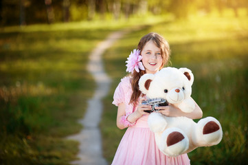 The girl-photographer in a pink dress hugging a teddy bear