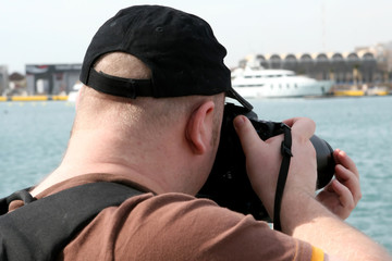 Close up of a photographer using a camera outdoors