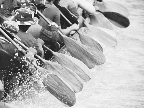 Wall mural Close up of rowing team race with black and white effect