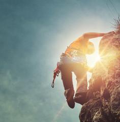 Man mountain climbing with a sunburst