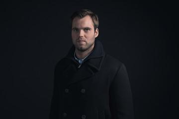 Stubbly bearded young man wearing dark blue winter coat.