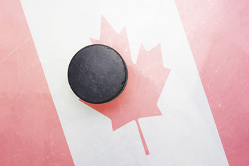 old hockey puck is on the ice with canada flag