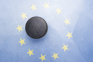 old hockey puck is on the ice with european union flag