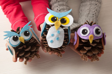 Children holding felt an pine cone owl craft