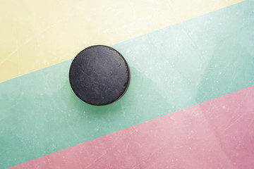 old hockey puck is on the ice with lithuania flag