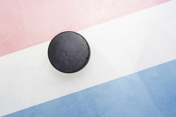 old hockey puck is on the ice with netherlands flag