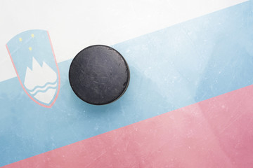 old hockey puck is on the ice with slovenia flag