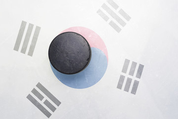 old hockey puck is on the ice with south korea flag