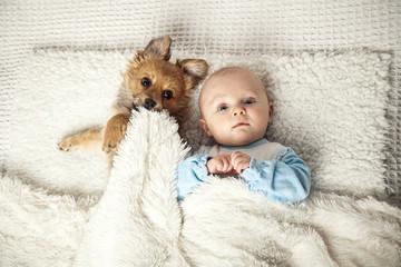 Baby schläft mit Welpe in einem Bett