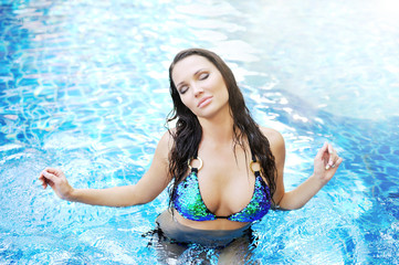 Young attractive woman relaxing in the pool