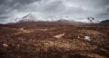 Wall Mural - The Scottish Highlands on a cloudy spring day with snowy Cuillin mountains - Isle of Skye, Scotland, UK