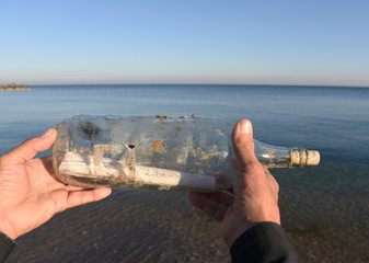 bottle with a message in man hands on the shore