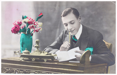 old photo  of young man writting a letter