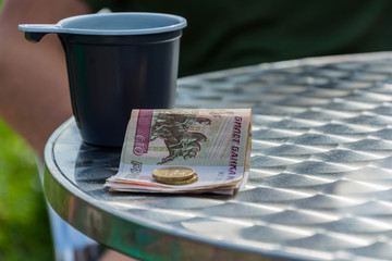 Money and the plastic mug on the edge of the table.