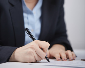 business woman writing in a notepad in the office