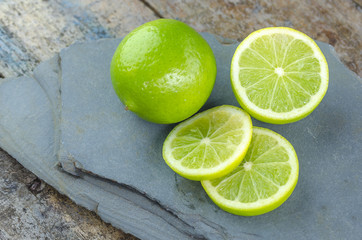 Tahitian limes on a stone background.