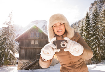 Smiling woman standing near mountain house and taking photos