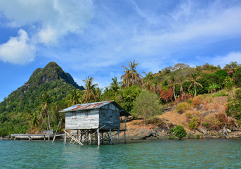 Exotic tropical Island with the Sea Gypsy house, Bodgaya Island, Semporna, Sabah Borneo, Malaysia. The island is the largest island in and forms part of the Tun Sakaran Marine Park.