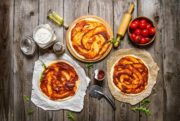Three pizzas spread tomato sauce the ingredients.