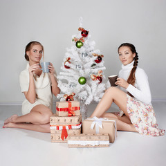 two beautiful girls with Christmas tree