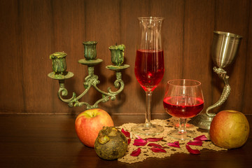 Still life image of red wine and fruits over wooden background