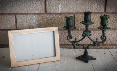 Photo frame and candlestick on wooden table over wall background