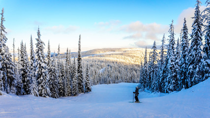 Skier watching the Sunset over the Shuswap Highlands at the Sun Peaks Ski Resort in central British Columbia