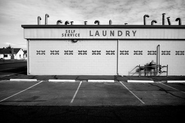 aged vintage photo of black and white public laundromat