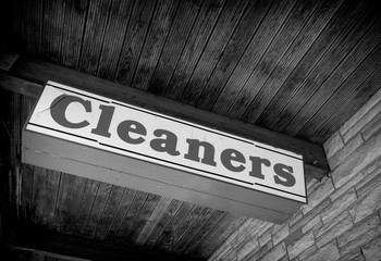 aged vintage photo of black and white cleaners sign