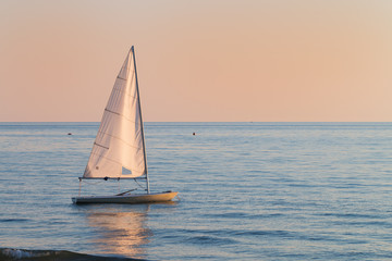 small sailboat in the water next to the beach